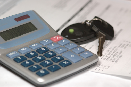 Calculator and car keys on papers