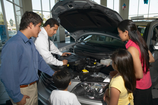 Car Salesman and Family Looking at Car Engine