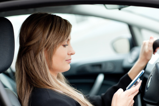 A woman using a phone while driving