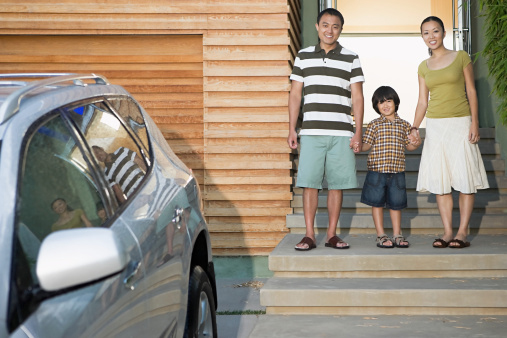 Family Standing in Front of Home and Car