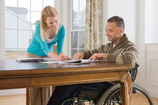 Woman Assisting Man in Wheelchair with Paperwork