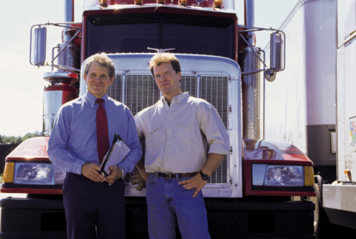 2 Men in Front of Semi Truck