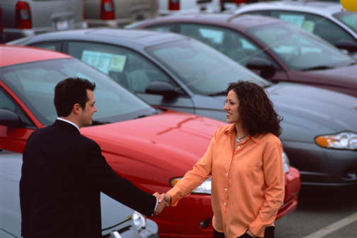 Woman and Man Shaking Hands at Car Dealership