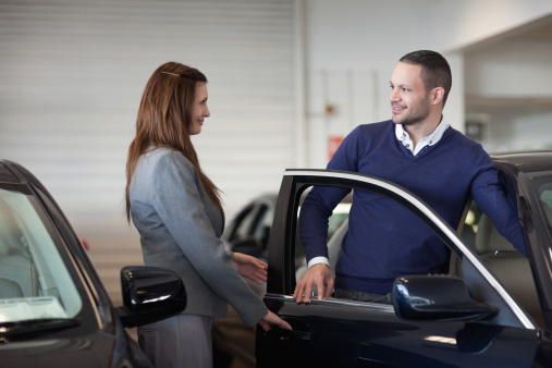 Saleswoman showing a car to a man