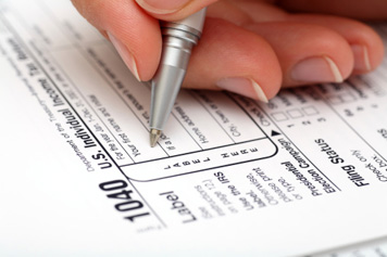 Hand Filling Out Tax Form