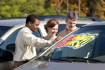 Car Salesman Showing Car to Couple