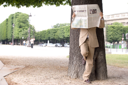 Spy hiding behin newsppaer in park